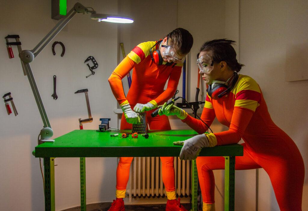 Kuvassa on kaksi Tuho-osasto esityksen oranssipukuista esiintyjää vihreän pöydän ääressä esineentuhoamistyössä.