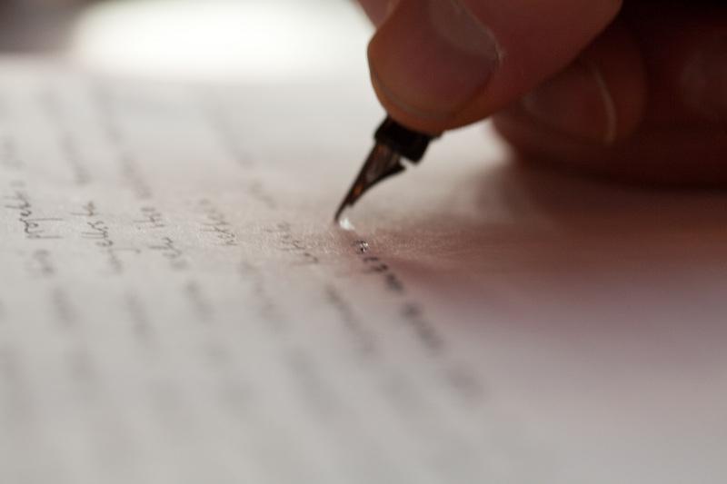 """""""II etydi ikuisesta elämästä – Kommunikaatio"""" Kuvassa on mustekynällä kirjoittava käsi."""
