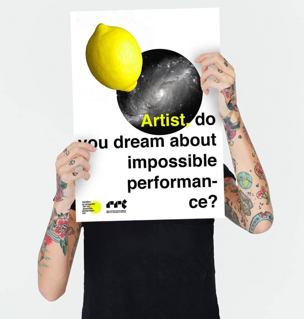 """Kuvassa on hahmo, jolla on tatuoidut kädet. Hahmo pitelee julistetta, jossa lukee """"Artist, do you dream about an impossible performance?)"""