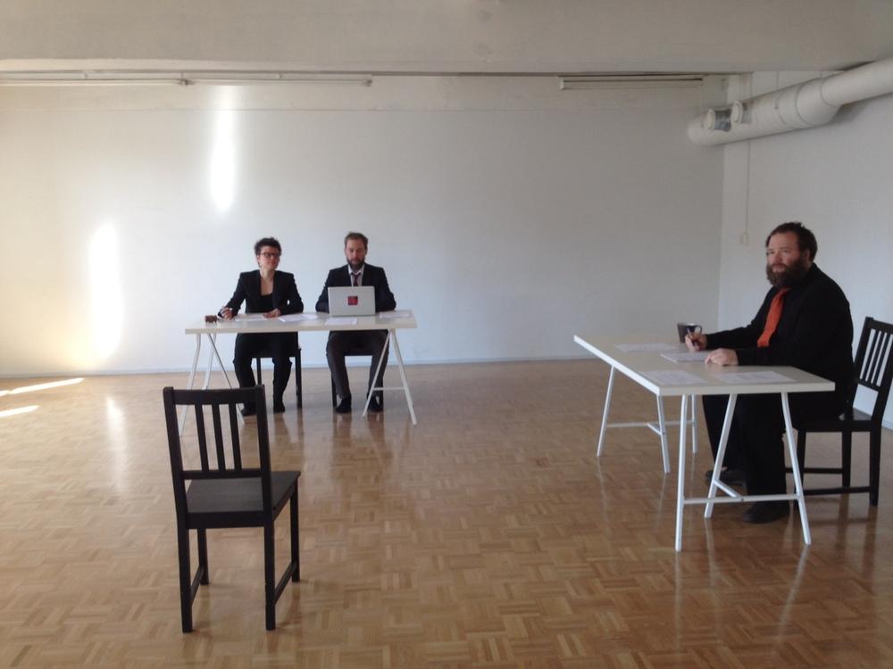Taidetuomioistuin. Salissa istuu pöytien ääressä ihmisiä. Keskellä on tyhjä yksittäinen tuoli.
