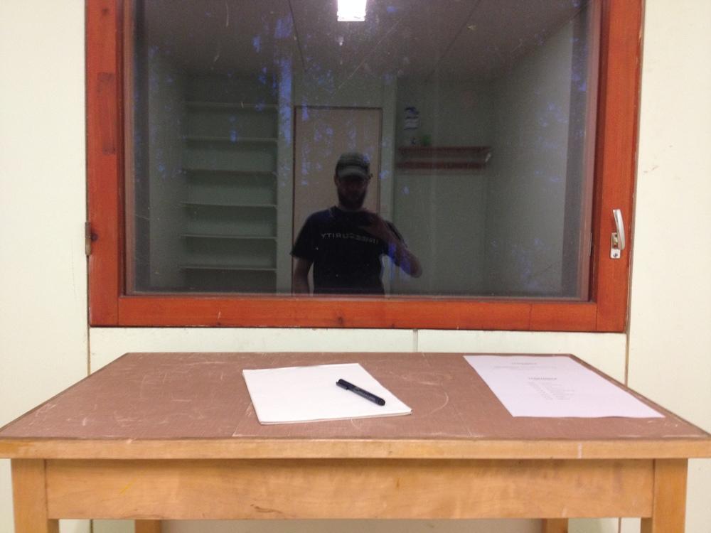 """""""Taidevankila aloitti toimintansa"""". Kuvassa on kirjoituspöytä, jonka takana olevasta ikkunasta heijastuu ihmisen siluetti."""