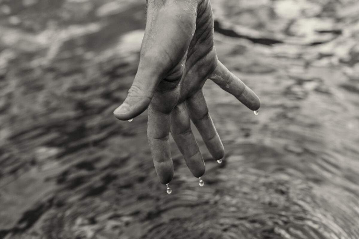 A hand above water with droplets dripping from the finger tips.