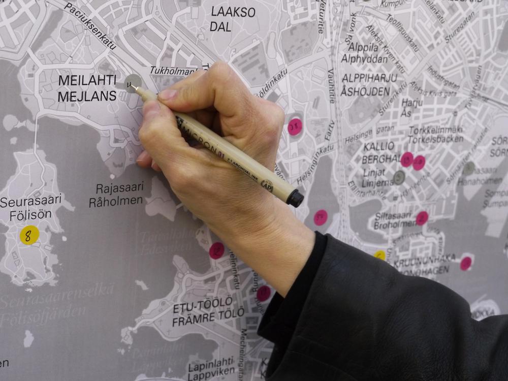 """""""UrbanUtopia"""". Käsi piirtämässä merkintää karttaan."""