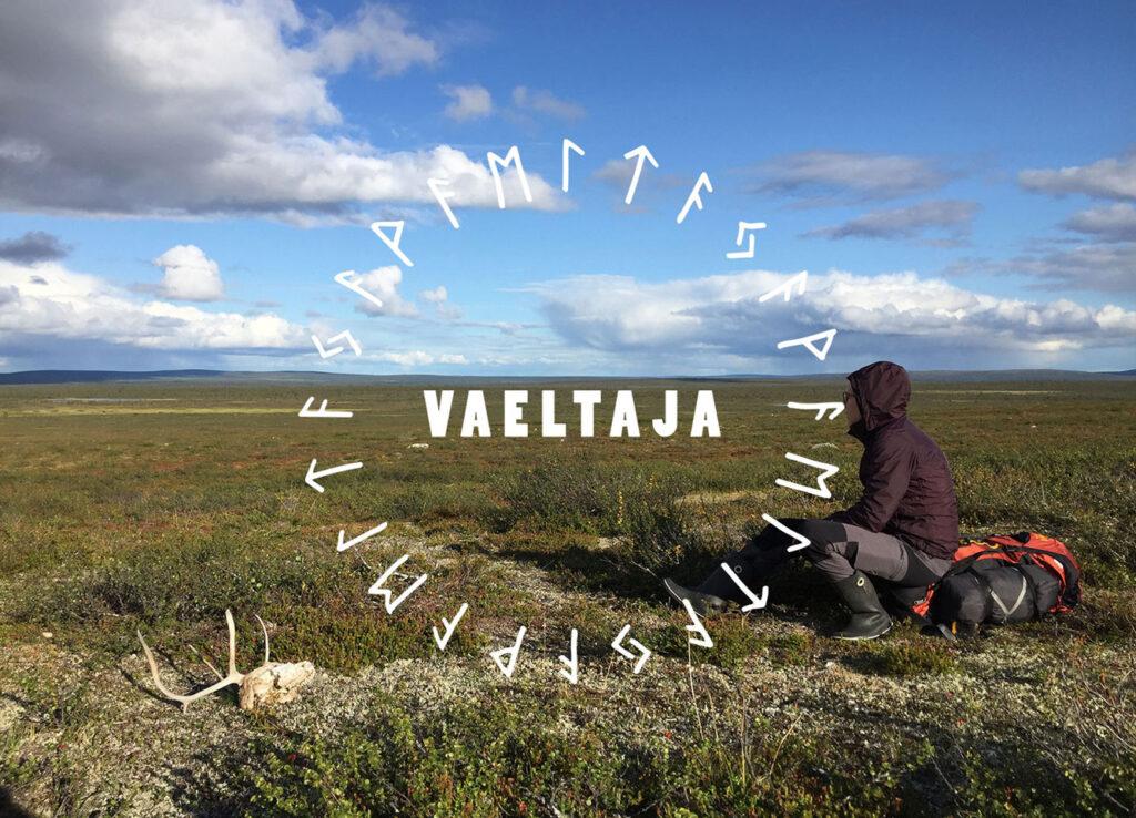 Kuvassa lukee Vaeltaja. Siinä näkyy erämaa-maisema, jonka oikeassa laidassa on istuva ihminen retkeilyasussa ja vasemmasssa laidassa valkoinen poron kallo.